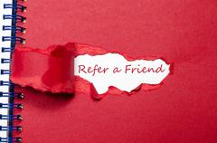 The word refer a friend appearing behind torn paper. Stock Photos