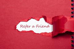 The word refer a friend appearing behind torn paper. - stock photo