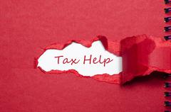 The word tax help appearing behind torn paper. Stock Photos