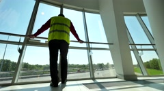 Man in Reflective Safety Vest standing against window of dispatch service Stock Footage