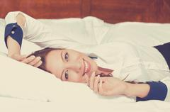 Cheerful young woman lying on the bed at home daydreaming resting. Wellbeing  - stock photo