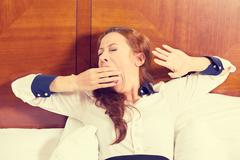 sleepy young business woman yawning lies in bed trying to wake up - stock photo