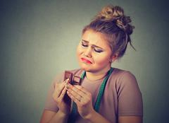 woman with measuring tape tired of diet restrictions craving sweets chocolate - stock photo