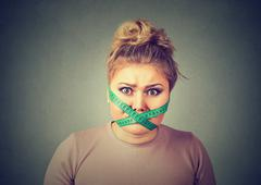 Diet restriction stress. Frustrated woman with measuring tape around her mout - stock photo