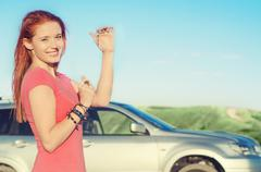 Happy car driver woman smiling showing new car keys and car on summer day - stock photo