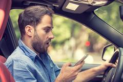 Man sitting in car with mobile phone in hand texting while driving Kuvituskuvat