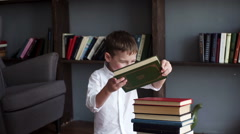 Little boy playing with books Stock Footage