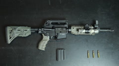 Overhead  of American sniper rifle on black table with magazine and three bullet Stock Footage