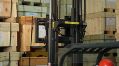 A worker uses a forklift to lift a wooden crate and move it down a long hallway. Stock Footage