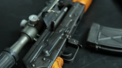 Handheld shallow focus close up accross an AK-47 and three rounds of ammo. Stock Footage