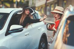 Woman insults another driver. Stock Photos
