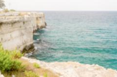 Defocused background with rocky cliffs in Salento, Italy - stock photo