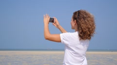 Travel Lifestyle. Female Tourist Taking Photo of Beach with Phone Stock Footage