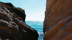 Young man jumping into paradise blue water from a high cliff - stock footage