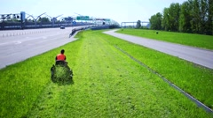 Aerial view of Road landscaper cutting grass along the modern highway Stock Footage