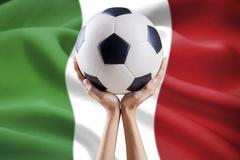 Hands hold ball with flag background of Italy - stock photo