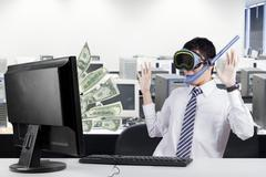 Happy businessman earns money from computer - stock photo