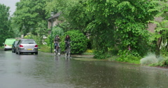 Extreme rain in netherlands, girls cyclists at flooded street Stock Footage