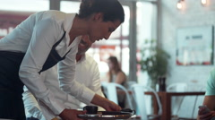 Waitress clearing table in cafe.. - stock footage