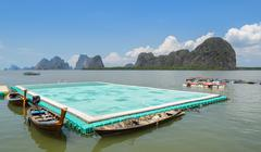 Green floating football pitch with beautiful limestone mountains background - stock photo