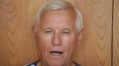 Senior man taking out false teeth Stock Footage