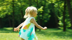 Baby girl 3 years old laughing and running from mother in the park Stock Footage