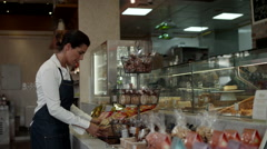 Waitress arranging food packets at cafe. - stock footage