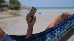 Young Woman with Mobile Phone in Hammock at Tropical Beach Stock Footage