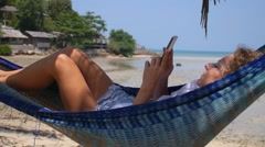 Woman Using Smartphone in Hammock on Beach Stock Footage