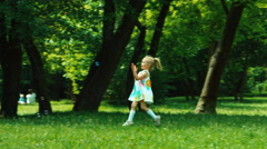 Baby girl 3 years old in white dress playing with soap bubbles in the park Stock Footage