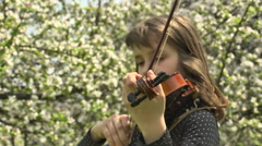 Girl Playing Violin in a Flowering Garden  Stock Footage