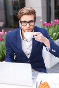 Handsome young male worker is resting in cafe - stock photo