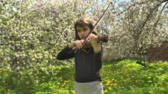 Girl Playing Violin in a Flowering Garden  - stock footage