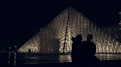 Lovers sitting on the fountaint at the musee du Louvre in Paris Stock Footage