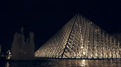 Musee du Louvre and fountain at night time in Paris Stock Footage
