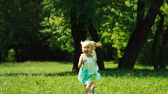Baby girl 3 years running at camera in the park and laughing Stock Footage