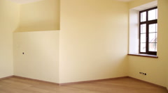 Empty decorated room with yellow walls, window, brown laminate, skirting board - stock footage