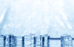 Melting transparent blue ice cubes on glass Stock Photos