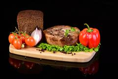 Meat medallion with vegetables on a wooden board - stock photo