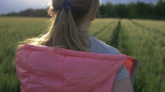 girl in a pink jacket runs on a wheat field at sunset, slow motion, back view - stock footage