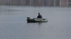 Fisherman catches a fish rod in the middle of the river in a rubber boat, 4k Stock Footage