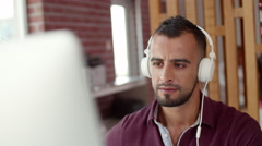 Expat businessman wearing headphones at office. Stock Footage