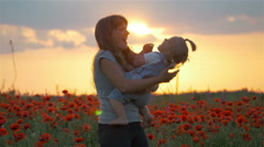 Mother hugs lovely child daughter in poppies field with sunset sunlight and Stock Footage