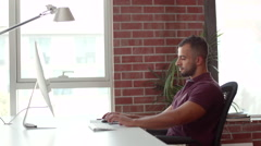 Expat businessman using computer and messaging on mobile at office. Stock Footage