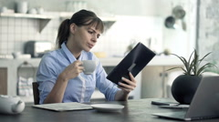 Young businesswoman reading news on tablet and drinking coffee by table in kitch Stock Footage