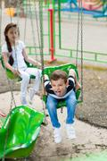 boy sitting on the carousel and showing tongue - stock photo