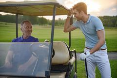 Golfer near golf cart - stock photo