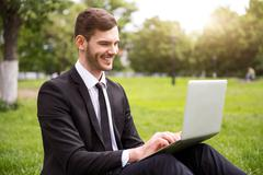 Handsome delighted man sitting on the grass - stock photo