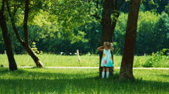 Children playing hide and seek. Baby girl child running in the park Stock Footage