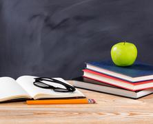 Back to school desk with stationery objects in front of erased black chalkboa Stock Photos